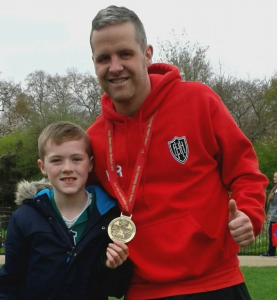 Karl Rolstone and his son with his London Marathon 2016 finishes medal